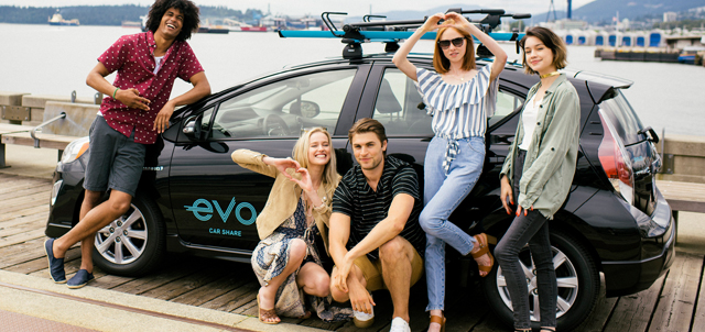 group of friends posing next to an evo car